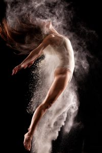 Amazing ballerina jumping and dancing in cloud of powder over black background